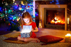 Little girl opening a magical Christmas gift Stock Photos