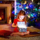 Little girl opening a magical Christmas gift Royalty Free Stock Images
