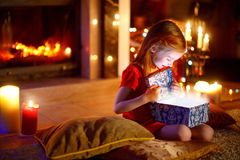 Little girl opening a magical Christmas gift Stock Images