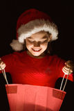 Little girl opening a magical christmas gift Royalty Free Stock Photo
