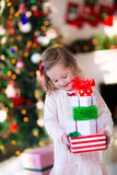 Little girl opening presents on Christmas morning Royalty Free Stock Photos