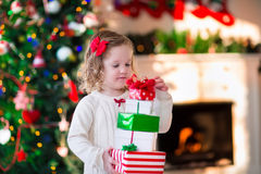 Little girl opening presents on Christmas morning Stock Photos