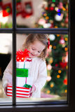 Little girl opening presents on Christmas morning Royalty Free Stock Images