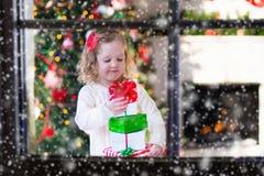 Little girl opening presents on Christmas morning Stock Image