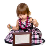 The little girl opens a box with a beads. Isolated on a white background Royalty Free Stock Image