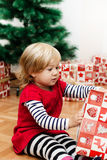 Little Girl Opens the Gift Royalty Free Stock Images