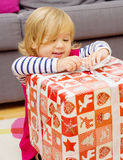 Little Girl Opens the Gift Stock Images