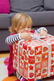 Little Girl Opens the Gift Stock Photos