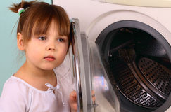 A little girl opens the washing machine Royalty Free Stock Photo