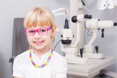 Little girl with optic glasses. Smiling royalty free stock photos