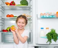 Little girl  against a refrigerator Stock Photos