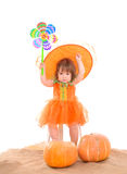 Little girl in orange costume with pumpkins Stock Images