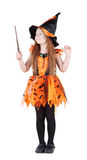 Little girl in orange costume of witch for Halloween. Holds and looks at wand isolated on white background Stock Photos