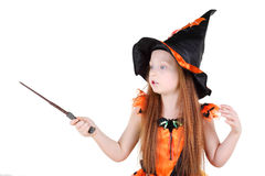 Little girl in orange costume of witch for Halloween. Holds wand and spell isolated on white background Royalty Free Stock Image
