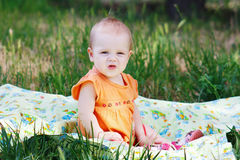 Little girl in orange dress sitting on a meadow Royalty Free Stock Image