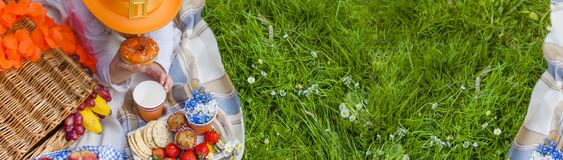 A little girl in an orange hat at a picnic in the garden, a meadow with flowers. Day of the King. Sweets and drinks. Spring in the stock image