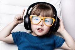A little girl in orange hipster glasses listens to music on headphones in the armchair of the house. Royalty Free Stock Images