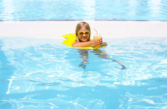 Little girl with orange juice in the pool Royalty Free Stock Photo