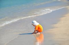 A little girl in an orange swimsuit sits on the beach on a sunny day. royalty free stock images