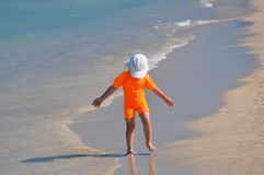 A little girl in an orange swimsuit is walking along the beach on a sunny day. stock image