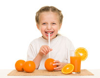 Little girl with oranges drink juice with a straw Royalty Free Stock Photo
