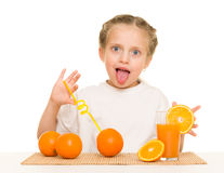 Little girl with oranges drink juice with a straw. Isolated royalty free stock image