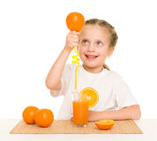 Little girl with oranges drink juice with a straw Stock Images