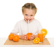 Little girl with oranges drink juice with a straw Royalty Free Stock Photography