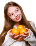 Little girl with oranges and juice Stock Images