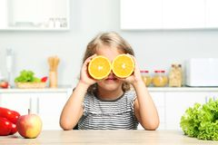 Girl with oranges. Little girl with oranges sitting in the kitchen Royalty Free Stock Image