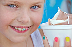 Little girl with orthodontic smile. Young Caucasian girl with orthodontic braces and ice cream in styrofoam cup Royalty Free Stock Photography