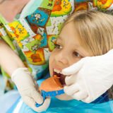 Little girl at the orthodontist. Orthtodontis preparing teeth mold for little girl Royalty Free Stock Image