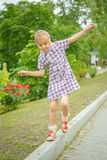 Little girl oscillates on curb Royalty Free Stock Photos