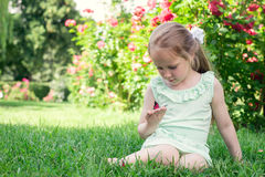 Little girl outdoor holds butterfly in her hand Royalty Free Stock Image