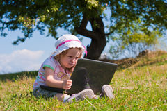 Little girl outdoor with laptop sitting on grass Stock Image