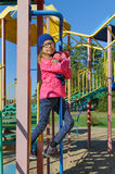 Little girl on outdoor playground equipment. Beautiful smiling cute pretty little girl on outdoor playground equipment Royalty Free Stock Images