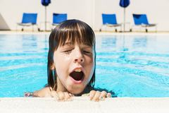 Little girl in an outdoor pool. Little girl with his mouth open and his eyes closed coming out of the water in an outdoor pool royalty free stock photo