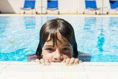 Little girl in an outdoor pool. Little girl looking at camera in an outdoor pool royalty free stock images