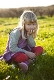Little girl outdoors. Cute little girl outdoors sitting on a green field with flowers stock image