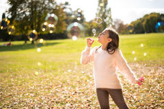 Little girl outdoors at beautiful autumn day blows soap bubbles Stock Photo