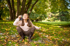 Little girl outdoors at beautiful autumn day blows soap bubbles Royalty Free Stock Image