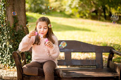 Little girl outdoors at beautiful autumn day blows soap bubbles Stock Images