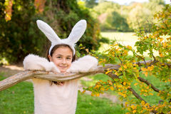 Little girl outdoors at beautiful autumn day with rabbit ears on her head Royalty Free Stock Photo