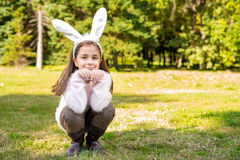 Little girl outdoors at beautiful autumn day with rabbit ears on her head Royalty Free Stock Photography