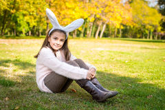 Little girl outdoors at beautiful autumn day with rabbit ears on her head Stock Photos