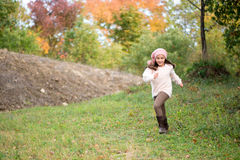 Little girl outdoors at beautiful autumn day running in the park Stock Photo