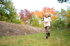 Little girl outdoors at beautiful autumn day running in the park royalty free stock image