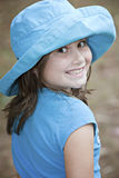 Little girl outdoors in blue hat Stock Photos