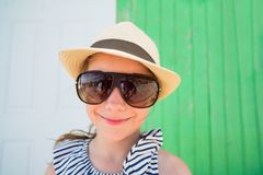 Little girl outdoors. Funny portrait of little girl wearing sun glasses and straw hat outdoors on summer day stock photography