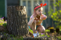 Little girl outdoors, makes the gesture of listening. Royalty Free Stock Image